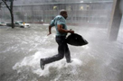 Arnold James tries to keep his feet as a strong gust nearly blows him over as he tries to make his way on foot to the Louisiana Superdome. The roof on James's home blew off, forcing him to seek shelter at the Superdome. AP Photo/Dave Martin